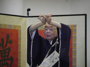 去年を表す漢字「北」を両手で示す森清範貫主